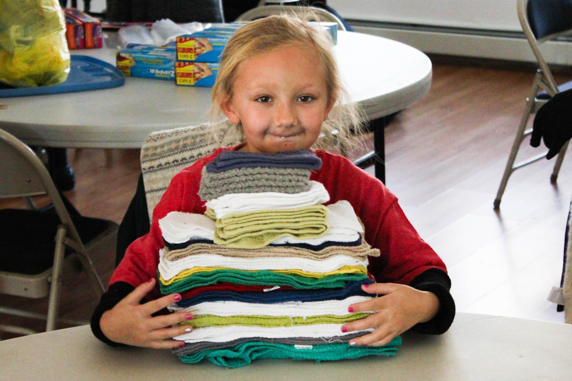 A young helper carries washcloths