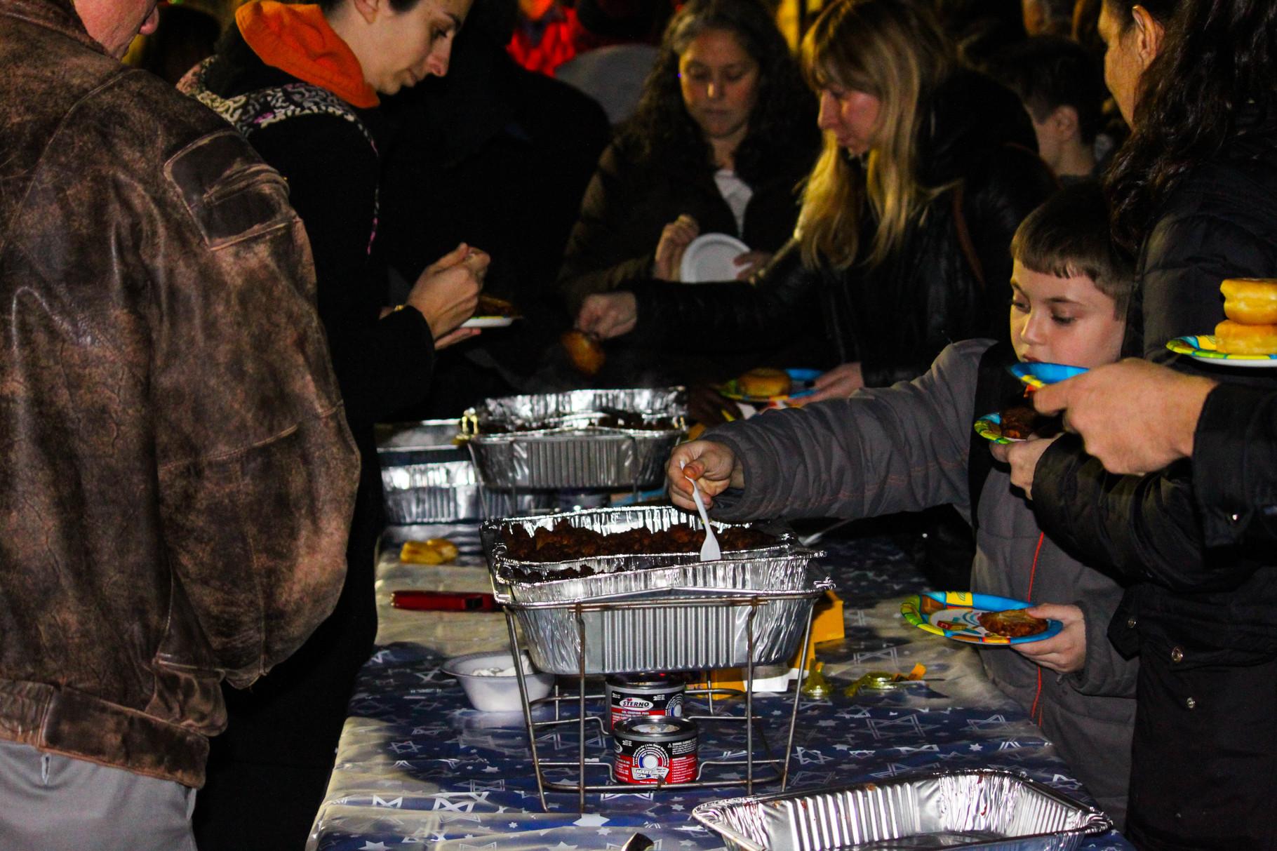 Residents enjoy hot latkes and donuts