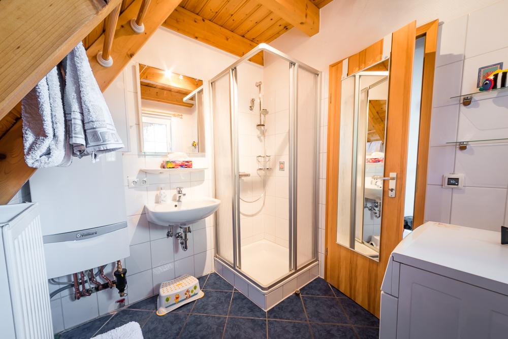 Badezimmer im Erdgeschoss mit Waschmaschine, Fön und großem Spiegel