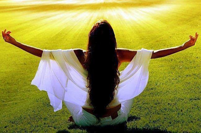 Mujer de espaldas sentada sobre la hierba con los brazos abiertos en cruz