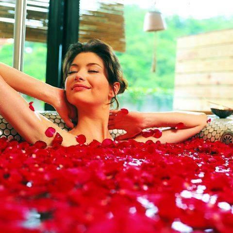 Mujer en baño con pétalos