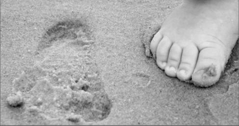 Pié derecho de un bebé caminando sobre la arena de la playa