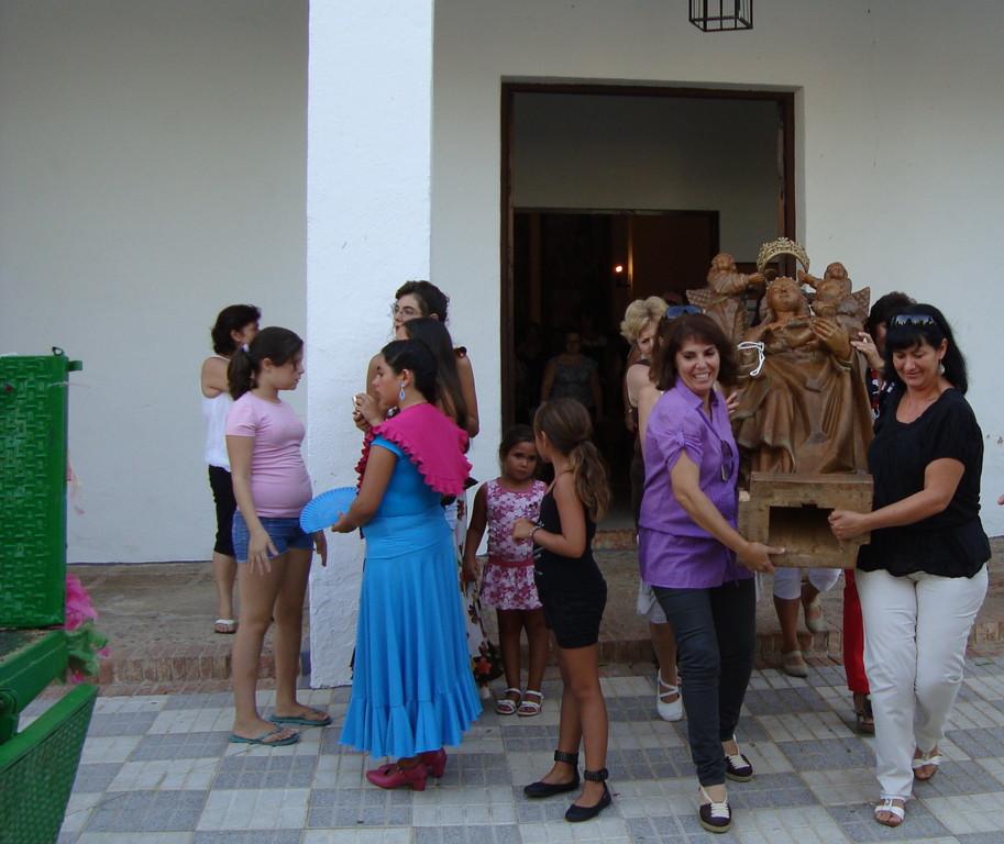 Las mujeres del pueblo llevan la imagen hasta la carroza