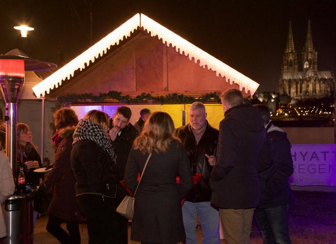 Weihnachtshütte mit dem Kölner Dom und fröhlichen Gästen