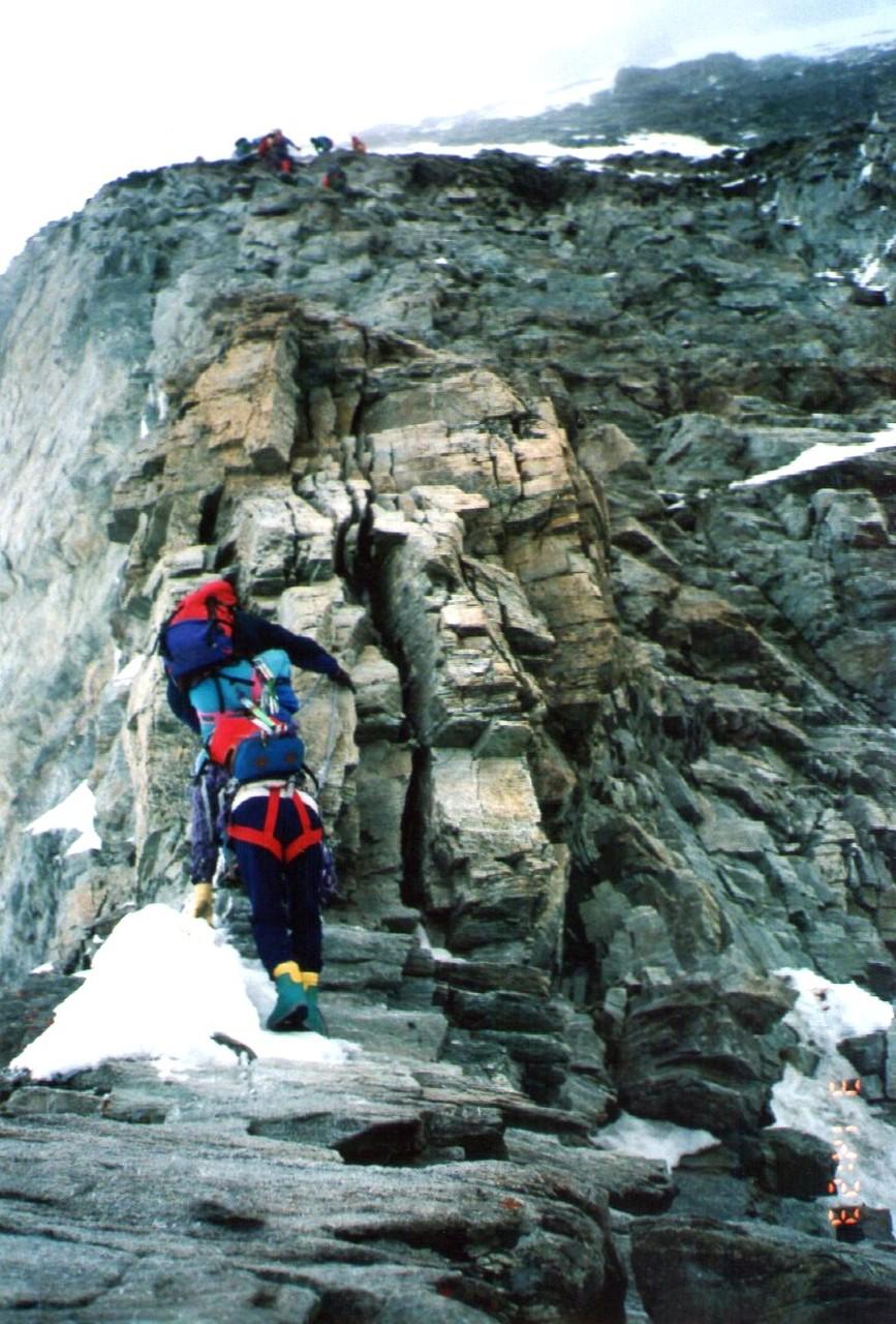 ソルベイ小屋6・50~7・10は一杯、気を取り直しカメラを出す。小屋の左の壁を登るとヘルンリ稜、肩の雪田は氷結しクランポンを着ける。4ピッチで抜け岩稜に戻ると太いフィックスロープ手のデカイ自分でもビックリ。雪稜をゆっくり進むスキーの十字架右にマリア様ガイドは最後のビレー点にしていた。