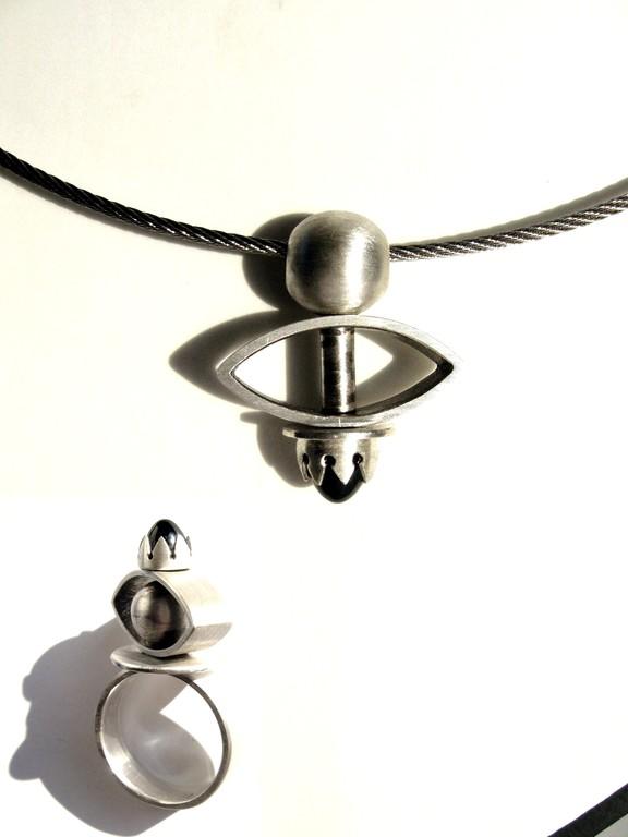 Ring und Anhänger, Material 925/- Sterlingsilber, geschwärzt. Die Navetteform ist beweglich. Beide Teile tragen als sich zugewantes Element einen Onyx.