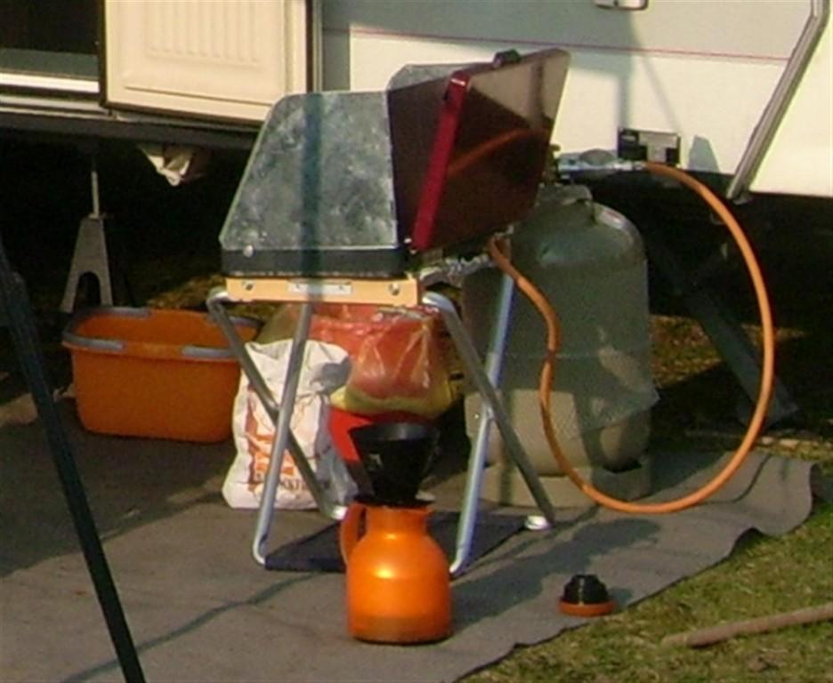 Untergestell für Mobilkocher: Holzrahmen und umgedrehter Klapphocker