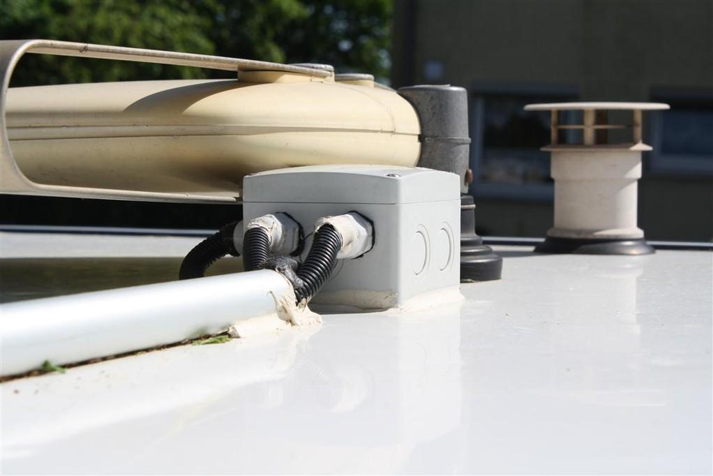 Aufgeklebtes Alurohr (ehem. Besenstiel) als Kabelrohr,  IP 65 Dose (Deckel verschraubt, Boden ausgeschnitten) mit Schraubnippeln aufgeklebt. Eigentliche Dachdurchführung mit eingeklebtem Kunststoffrohr, daß über das Dach in die Dose reinreicht.
