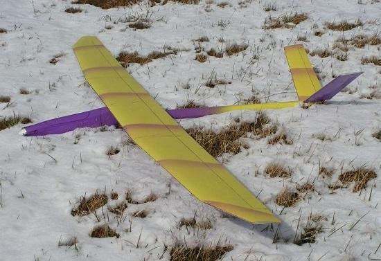 planeur Aldij Aeromod jaune violet posé dans la neige