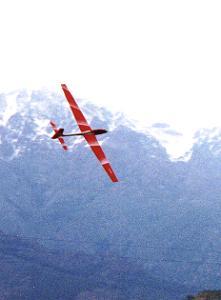 planeur Voltij Aeromod blanc et rouge en vol à la montagne