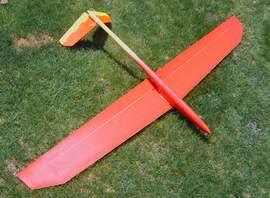 planeur minij aeromod jaune et rouge posé à l'envers dans l'herbe