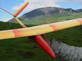 planeur minij aeromod jaune et rouge dans la main à la montagne