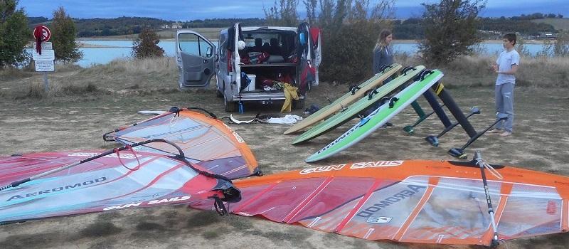 au lac de la Ganguise, trois planches en cours de démontage avec les 3 windfoils Aeromod, les 3 voiles à côté,  deux adolescents, une fourgonette en cours de rangement