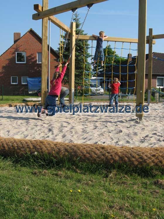 Spielplatzwalzen trennen Rasenfläche und Sandbereich