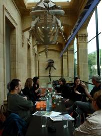 Une photo d'une réunion de travail sous un squelette de baleine